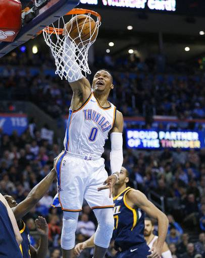 Oklahoma City Thunder guard Russell Westbrook (0) dunks in front of Utah Jazz center Rudy Gobert, right, in the second quarter of an NBA basketball game in Oklahoma City, Tuesday, Dec. 5, 2017. (AP Photo/Sue Ogrocki)