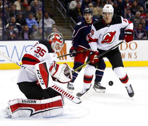 New Jersey Devils goalie Cory Schneider, left, stops a shot in front of Columbus Blue Jackets forward Artemi Panarin, center, of Russia, and Devils New Jersey Devils defenseman Steven Santini during the second period of an NHL hockey game in Columbus, Ohio, Tuesday, Dec. 5, 2017. (AP Photo/Paul Vernon)