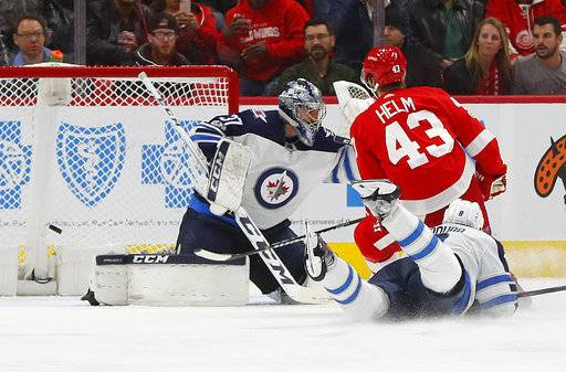 Detroit Red Wings left wing Darren Helm (43) scores on Winnipeg Jets goalie Connor Hellebuyck (37) in the third period of an NHL hockey game Tuesday, Dec. 5, 2017, in Detroit. (AP Photo/Paul Sancya)