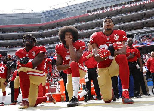"FILE - In this Oct. 2, 2016, file photo, San Francisco 49ers outside linebacker Eli Harold, left, quarterback Colin Kaepernick, center, and safety Eric Reid kneel during the national anthem before the team's NFL football game against the Dallas Cowboys in Santa Clara, Calif. Kaepernick accepted Sports Illustrated's Muhammad Ali Legacy Award from Beyonce on Tuesday night, Dec. 5, 2017, and promised that ""with or without the NFL's platform, I will continue to work for the people."" Beyonce thanked Kaepernick for his ""personal sacrifice,"" and 2016 Ali Award winner Kareem Abdul-Jabbar called Kaepernick a ""worthy recipient"" during a video tribute.(AP Photo/Marcio Jose Sanchez, File)"