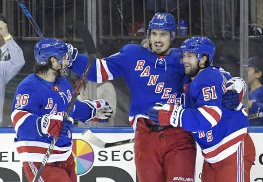 New York Rangers center David Desharnais (51) celebrates his goal with Chris Kreider (20) and Mats Zuccarello (36) during the second period of an NHL hockey game against the Carolina Hurricanes on Friday, Dec. 1, 2017, at Madison Square Garden in New York. (AP Photo/Bill Kostroun)