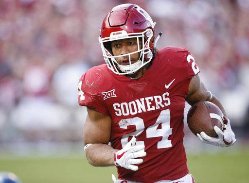 FILE - In this , Saturday, Nov. 25, 2017 file photo, Oklahoma running back Rodney Anderson (24) carries in the second quarter of an NCAA college football game against West Virginia in Norman, Okla. Anderson, one of Oklahoma's breakout stars this year, is accused of sexual assault. (AP Photo/Sue Ogrocki, File)