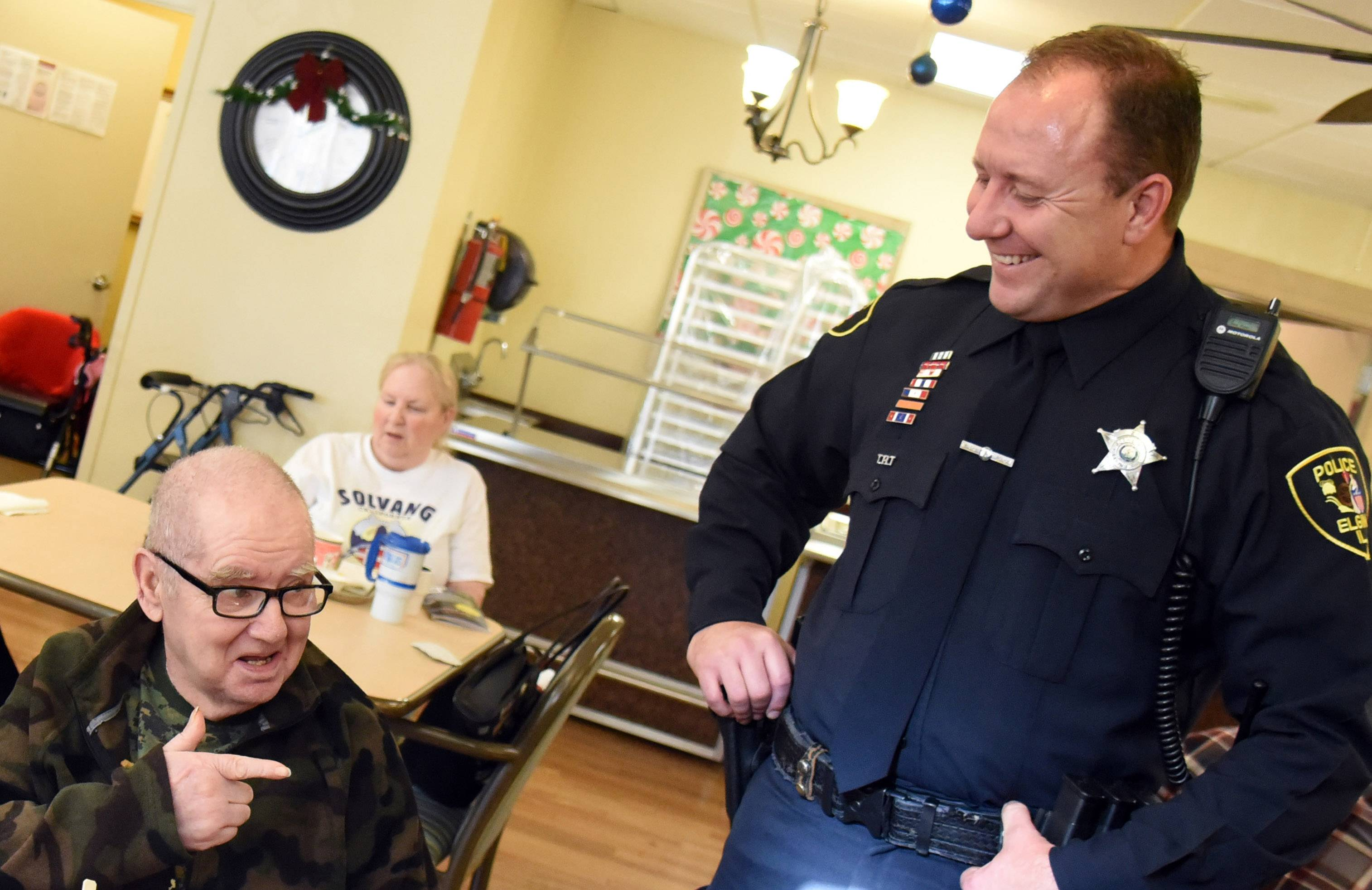"Elgin police officer Jason Lentz visits James ""Jim"" May on Wednesday at the River View Rehab Center in Elgin. Lentz saved May's life Thanksgiving Day when he did the Heimlich maneuver after May choked on turkey."