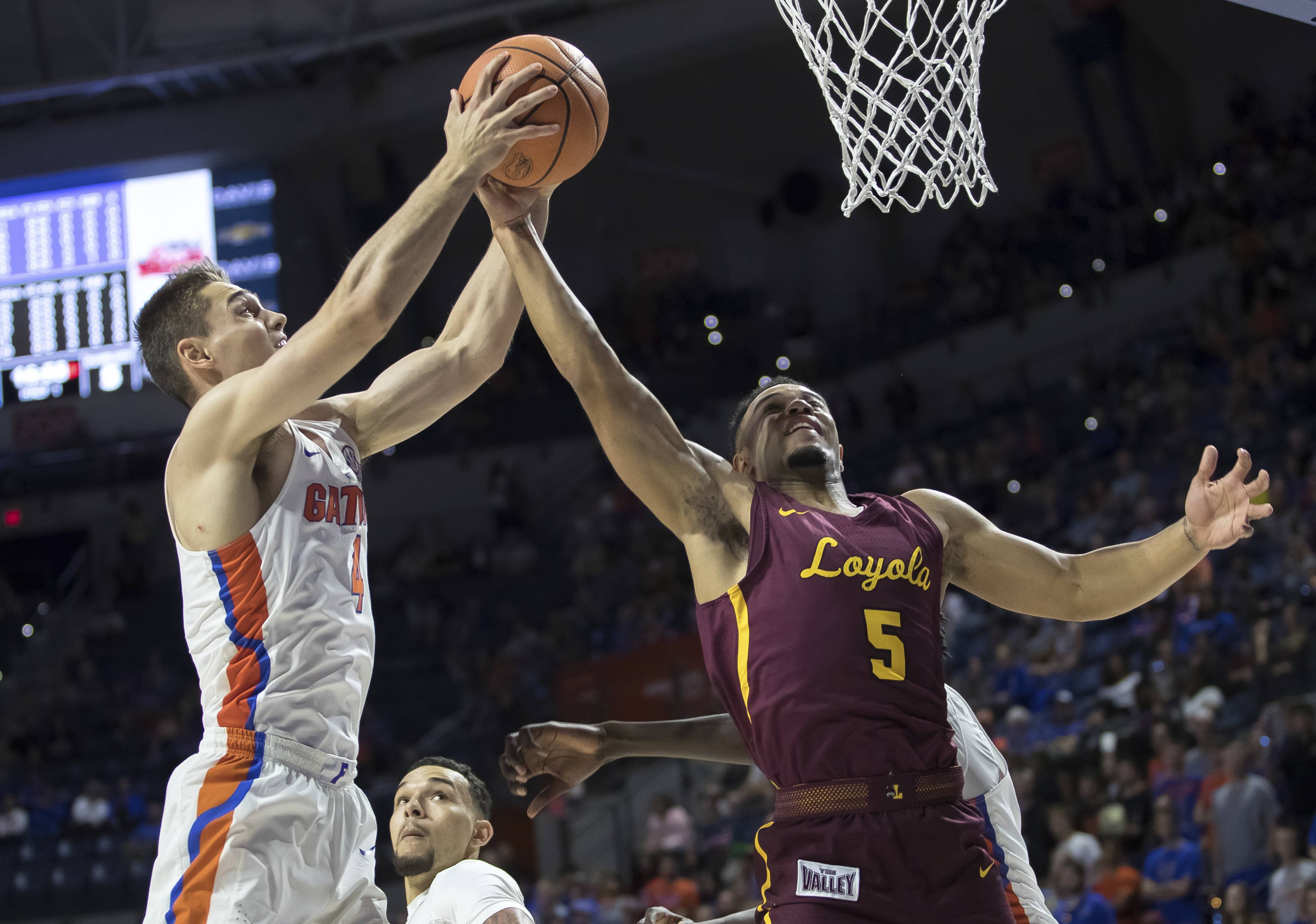 Florida guard Egor Koulechov (4) and Loyola of Chicago guard Marques Townes (5) battle for a rebound during the first half of an NCAA college basketball game in Gainesville, Fla., Wednesday, Dec. 6, 2017. (AP Photo/Ron Irby)