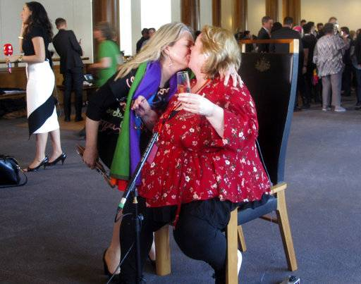 Australian Sen. Louise Pratt, left, kisses actress Magda Szubanski at Parliament House in Canberra, Australia, Thursday, Dec. 7, 2017. The Parliament voted Thursday to allow same-sex marriage across the nation, following a bitter debate settled by a much-criticized government survey of voters that strongly endorsed change.