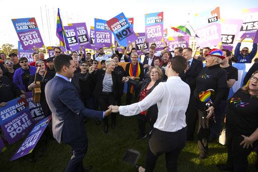 Same-sex marriage campaigners and volunteers cheer as they call on politicians to pass marriage equality legislation during rally outside Parliament House in Canberra, Australia, Thursday, Dec. 7, 2017. Gay marriage was endorsed by 62 percent of Australian voters who responded to a government-commissioned postal ballot by last month. (Lukas Coch/AAP Image via AP)