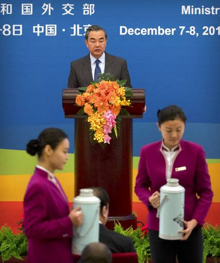 Hostesses serve flasks of hot water for tea as Chinese Foreign Minster Wang Yi speaks during the South-South Human Rights Forum at the Great Hall of the People in Beijing, Thursday, Dec. 7, 2017. China opened a human rights forum attended by developing countries Thursday in its energetic drive to showcase what it considers the strengths of its authoritarian political system under President Xi Jinping.