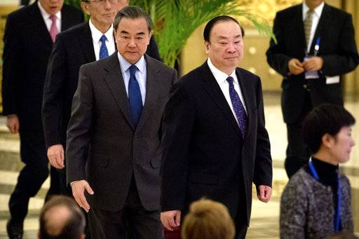 Chinese Foreign Minister Wang Yi, center left, and Huang Kunming, center right, minister of the Propaganda Department of the Communist Party of China (CPC) Central Committee, arrive for the South-South Human Rights Forum at the Great Hall of the People in Beijing, Thursday, Dec. 7, 2017. China opened the human rights forum attended by developing countries Thursday in its energetic drive to showcase what it considers the strengths of its authoritarian political system under President Xi Jinping.
