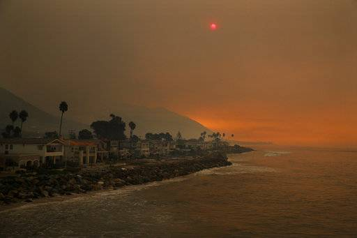 Homes stand along the beach as the sun is visible through thick smoke from a wildfire Wednesday, Dec. 6, 2017, in Ventura, Calif. A dramatic new wildfire erupted in Los Angeles early Wednesday as firefighters battled three other destructive blazes across Southern California.