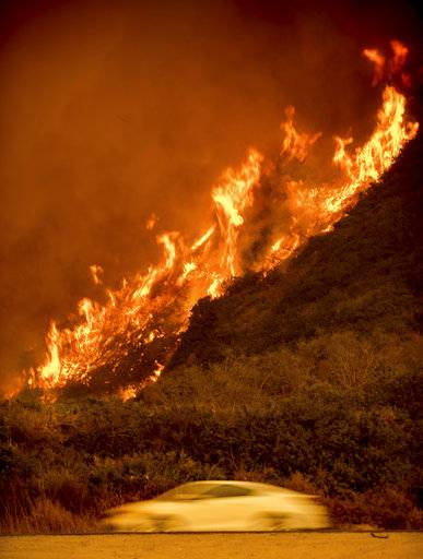 Flames from the Thomas fire burn above traffic on Highway 101 north of Ventura, Calif., on Wednesday, Dec. 6, 2017.