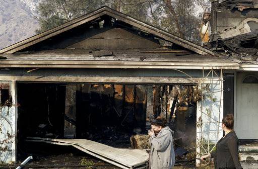 Neighbors walk past a home destroyed by wildfire along Via San Anselmo in the Sylmar area of Los Angeles Wednesday, Dec. 6, 2017.