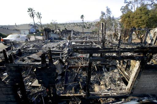 The remains of a wildfire destroyed home smolders along Via San Anselmo in the Sylmar area of Los Angeles Wednesday, Dec. 6, 2017.