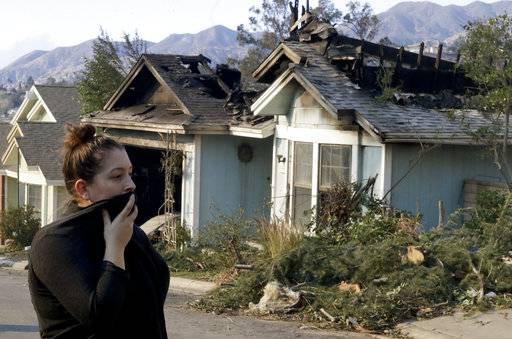 Crystal Shore look over the wildfire damaged neighbors home along Via San Anselmo in the Sylmar area of Los Angeles Wednesday, Dec. 6, 2017.