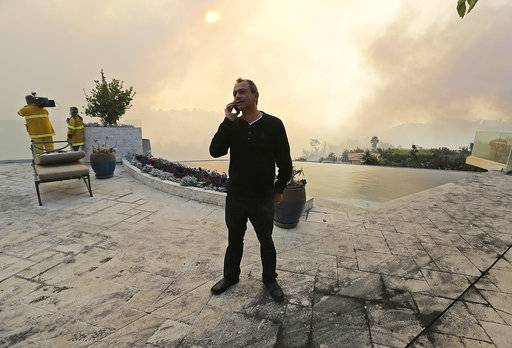 "Maurice Kaboud makes a phone call after a wildfire threatened his home in the Bel Air district of Los Angeles Wednesday, Dec. 6, 2017. When firefighters told Kaboud to evacuate, he decided to stay and protect his home. The 59-year-old stood in the backyard of his multimillion- dollar home as the Skirball fire raged nearby. ""God willing, this will slow down so the firefighters can do their job,"" Kaboud said."