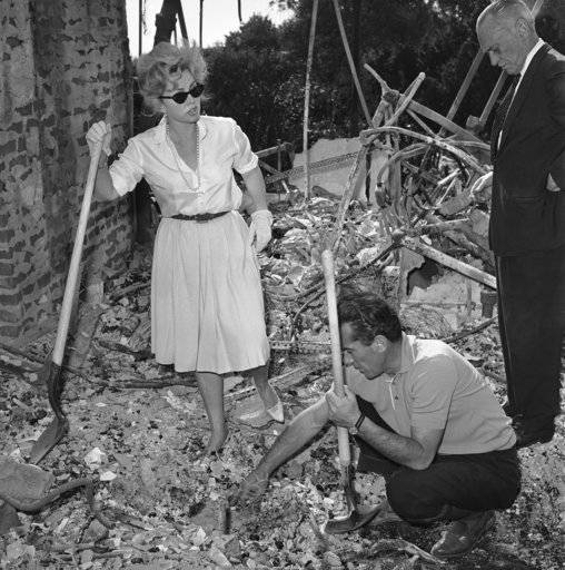File - In this Nov. 8, 1961 file photo, Zsa Zsa Gabor, aided by a friend, Robert Straile, digs through the ashes of her $275,000 Bel-Air home in Los Angeles. Nearly 500 homes burned in the area during the infamous Bel Air Fire of 1961. Celebrities, including Burt Lancaster and Zsa Zsa Gabor, lost homes in the fire.