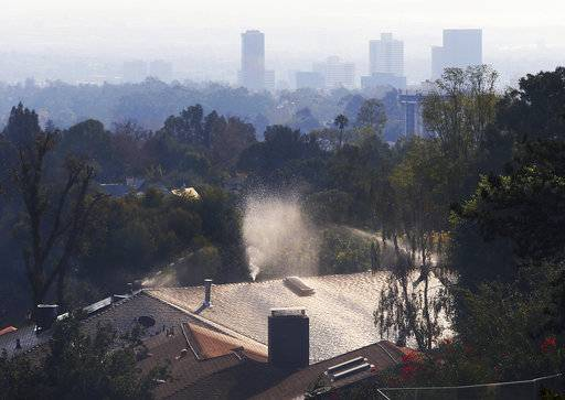 With the west Los Angeles skyline in the background, sprinklers wet down the roof of a home after a wildfire swept through the Bel Air district of Los Angeles Wednesday, Dec. 6, 2017.