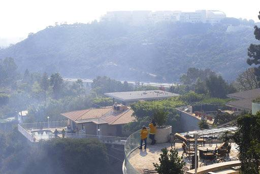 The Getty Center lies shrouded in smoke as firefighters keep watch on a nearby canyon from the terraces of homes in the Bel Air district of Los Angeles after the Skirball wildfire swept through Wednesday, Dec. 6, 2017. A destructive wildfire that erupted early Wednesday burned not far from The Getty Center, the $1 billion home to the J. Paul Getty Museum and related organizations that overlooks Los Angeles from a perch on the southern slope of the Santa Monica Mountains.