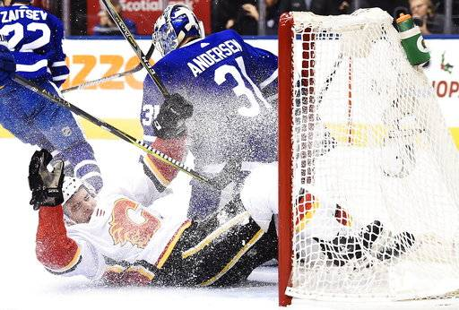 Calgary Flames right wing Garnet Hathaway (21) slides into Toronto Maple Leafs goalie Frederik Andersen's (31) net during the first period of an NHL hockey game, Wednesday, Dec. 6, 2017 in Toronto. (Nathan Denette/The Canadian Press via AP)