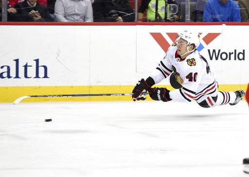 Chicago Blackhawks right wing John Hayden (40) falls to the ice during the second period of an NHL hockey game against the Washington Capitals, Wednesday, Dec. 6, 2017, in Washington.