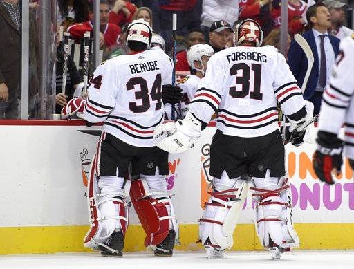 Chicago Blackhawks goalie Anton Forsberg (31), of Sweden, leaves the game after giving up three goals during the first period of an NHL hockey game against the Washington Capitals, Wednesday, Dec. 6, 2017, in Washington. Also seen is Chicago Blackhawks goalie J.F. Berube (34), who replaced Forsberg.