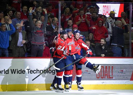 Washington Capitals left wing Alex Ovechkin, center, of Russia, celebrates his goal with center Nicklas Backstrom (19), of Sweden, and Washington Capitals defenseman Matt Niskanen, right, during the first period of an NHL hockey game against the Chicago Blackhawks, Wednesday, Dec. 6, 2017, in Washington.