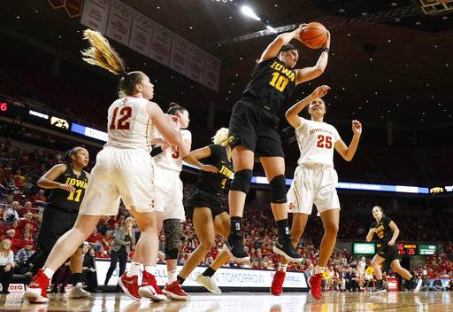 Iowa forward Megan Gustafson (10) grabs a rebound next to Iowa State's Bride Kennedy-Hopoate (12) and Kristin Scott (25) during the first half of an NCAA college basketball game Wednesday, Dec. 6, 2017, in Ames, Iowa.