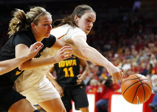 Iowa guard Makenzie Meyer, left, reaches for the ball with Iowa State guard Bridget Carleton during the first half of an NCAA college basketball game Wednesday, Dec. 6, 2017, in Ames, Iowa.