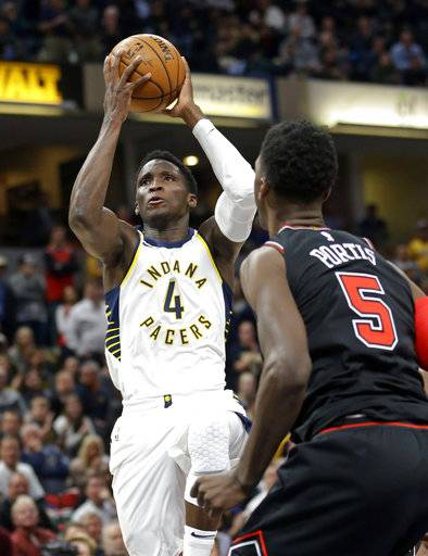 Indiana Pacers guard Victor Oladipo (4) shoots over Chicago Bulls forward Bobby Portis (5) during the second half of an NBA basketball game in Indianapolis, Wednesday, Dec. 6, 2017. The Pacers defeated the Bulls 98-96.