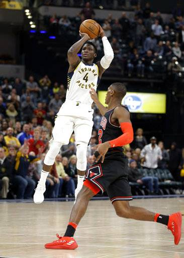 Indiana Pacers guard Victor Oladipo (4) hits a shot over Chicago Bulls guard Kris Dunn (32) to give the Pacers the lead in the final minute of an NBA basketball game in Indianapolis, Wednesday, Dec. 6, 2017. The Pacers defeated the Bulls 98-96.