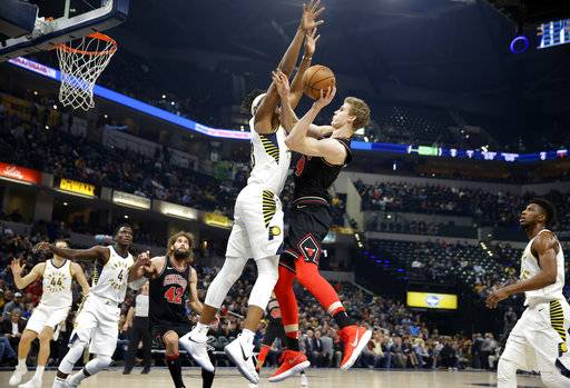 Chicago Bulls forward Lauri Markkanen (24) shoots over Indiana Pacers center Myles Turner during the first half of an NBA basketball game in Indianapolis, Wednesday, Dec. 6, 2017.
