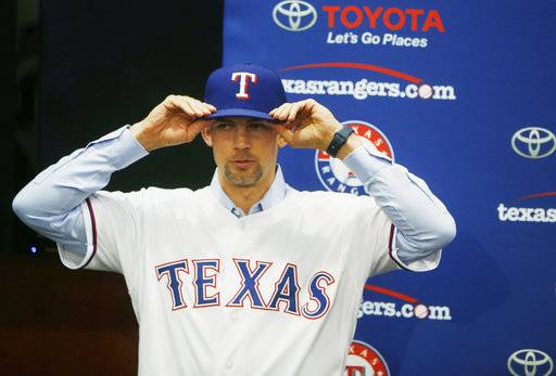 Newly signed Texas Rangers pitcher Mike Minor puts on a Rangers baseball cap before a press conference at Globe Life Park in Arlington, Texas, Wednesday, Dec. 6, 2017. A day after meeting in Los Angeles with Japanese pitcher and outfielder Shoehi Ohtani, Rangers officials were back home in Texas and introduced left-hander Mike Minor. The likely starter signed a $28 million, three-year contract. (Rose Baca/The Dallas Morning News via AP)