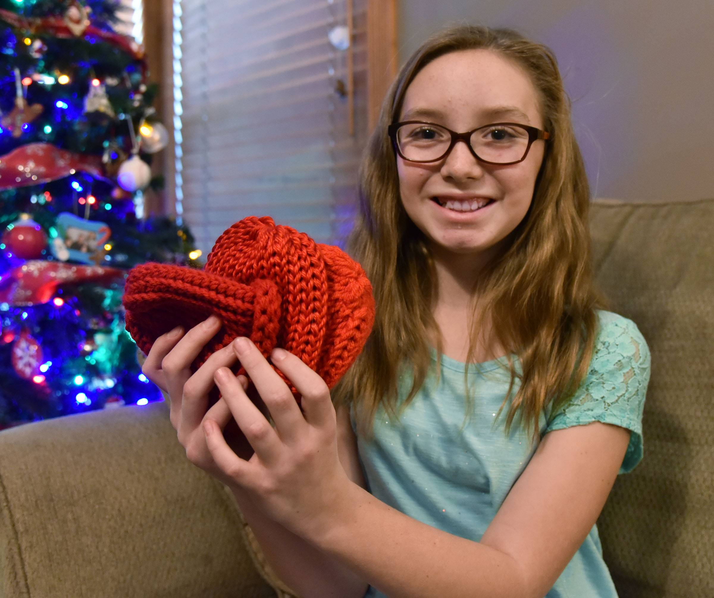 Emily Cavallini, 10, is using a loom to make tiny red hats in her South Elgin home for babies born during American Heart Month.