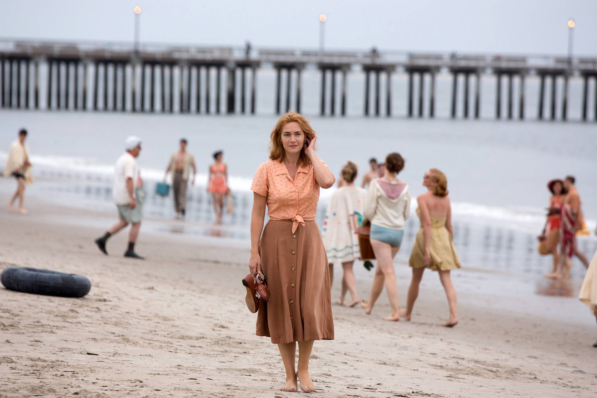"Ginny (Kate Winslet) strolls the beach in Woody Allen's ""Wonder Wheel."""