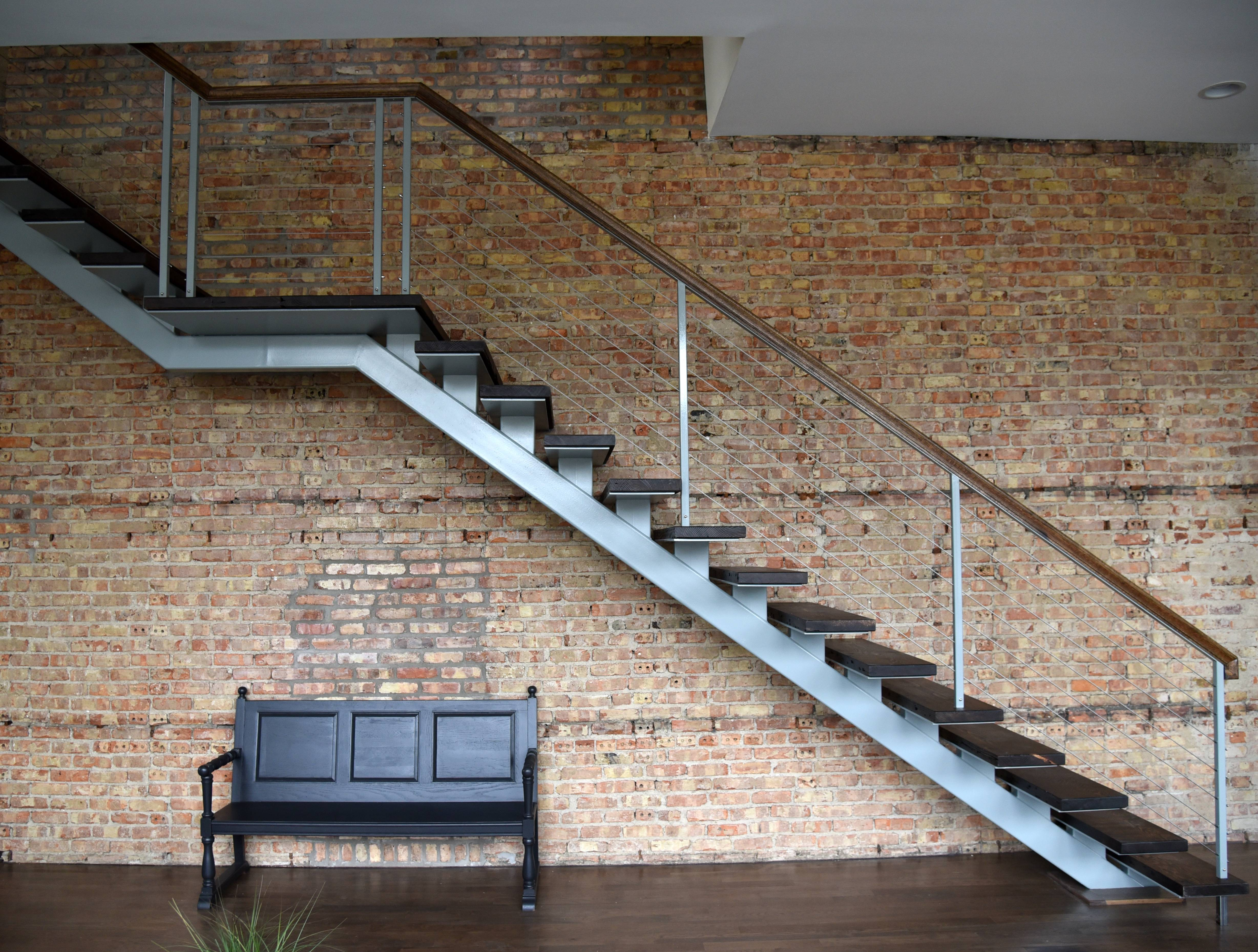 An exposed brick wall and new staircase highlight the downstairs rehab being done at the former Blaine Street School, a 111-year-old building in Batavia.
