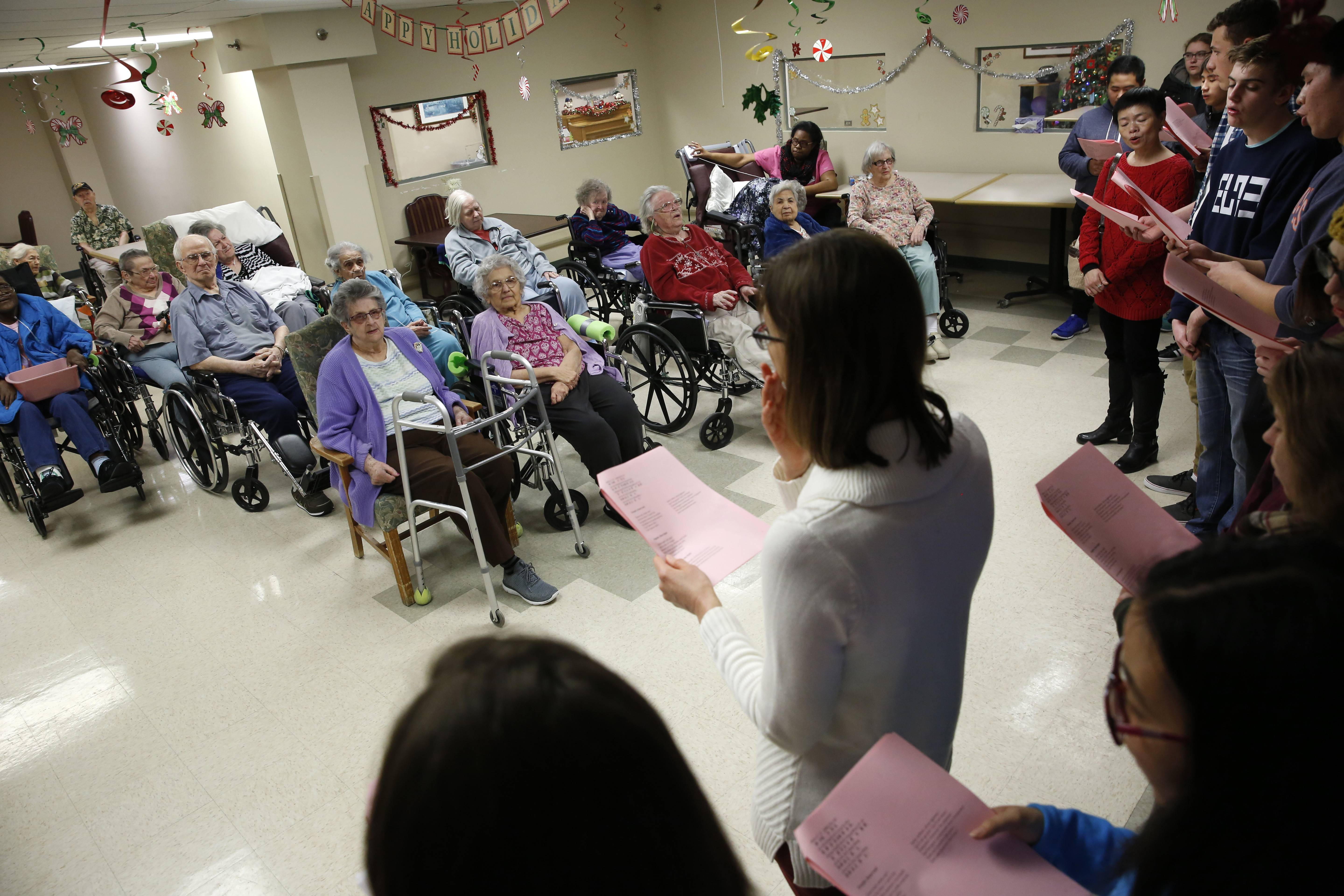 Naperville North High School students who study foreign languages sing holiday carols in Latin, German, Chinese, Spanish, Italian and French to residents at Community Nursing and Rehab in Naperville.