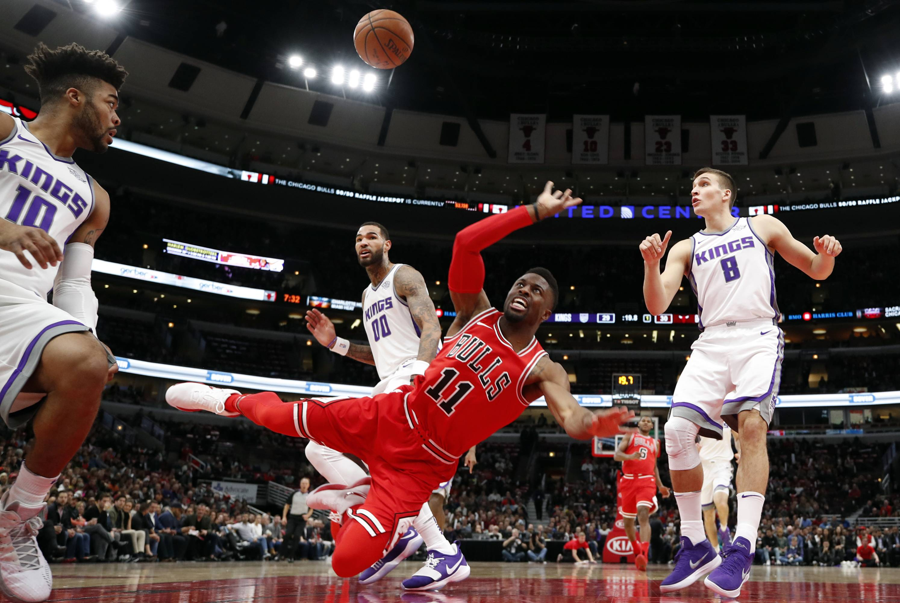 Chicago Bulls guard David Nwaba (11) falls to the floor as he shoots while Sacramento Kings players Frank Mason III (10), Willie Cauley-Stein (00) and Bogdan Bogdanovic (8) watch during the first half of an NBA basketball game in Chicago, Friday, Dec. 1, 2017.