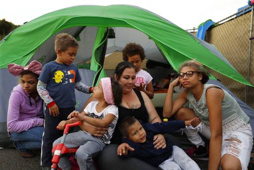 In this Nov. 8, 2017, photo, Christine Wade sits among her children in front of their donated tent in the city-sanctioned encampment on a parking lot in San Diego. They are, from left, Shawnni, 12, Roland, 4, Rayahna, 3, Jaymason, 2, Brooklyn, 8, and Shaccoya, 14. The Wade family is among several hundred people living in the city's first campground open for the homeless, set up to curb the worst Hepatitis A outbreak in the United States in decades.