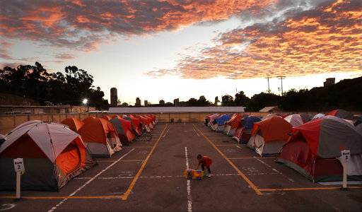 In this Nov. 8, 2017, photo, a boy plays as the sun sets over donated tents for homeless families lined up on a parking lot in the city-sanctioned encampment in San Diego. A parking lot in San Diego's famed Balboa Park has acted for the past two months as an unusual triage center. Scores of tents, mobile medical units, portable toilets and showers were brought in to meet the needs of hundreds of people affected by a societal problem that has bloomed into a deadly disaster: Homelessness.