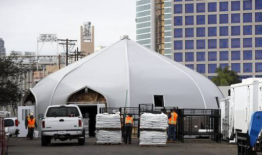 In this Nov. 28, 2017, photo, a tent to house the homeless is seen in downtown San Diego. An unprecedented increase in people living on the streets is rocking cities along the West Coast from Washington to California. Facing an acute shortage of housing for the poor, San Diego is turning to tents to get people off the streets for now. The city diverted $6.5 million from its permanent housing budget to operate the giant tents.