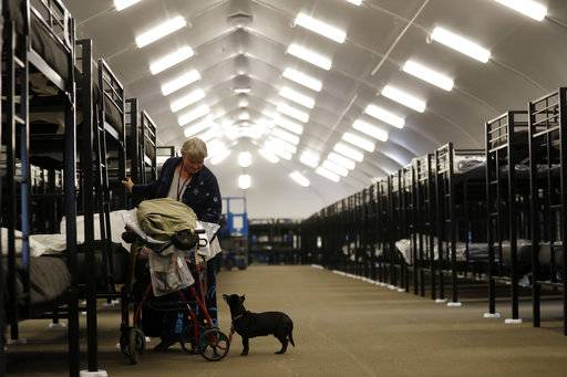In this Dec. 1, 2017 photo, Verna Vasbinder prepares her her new bunk in the city's new Temporary Bridge Shelter for the homeless as her dog, Lucy Lui, looks on in downtown San Diego. Facing an acute shortage of housing for the poor, San Diego is turning to tents to get people off the streets for now. The city diverted $6.5 million from its permanent housing budget to operate the giant tents.