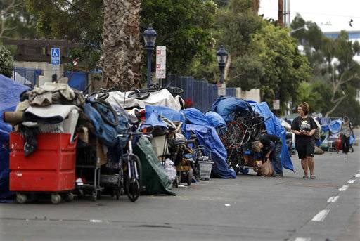 "In this Sept. 19, 2017 photo, trash from homeless encampments lines a street in San Diego. In a place that bills itself as ""America's Finest City,� renowned for its sunny weather, surfing and fish tacos, spiraling real estate values have contributed to spiraling homelessness in San Diego. Most alarmingly, the explosive growth in the number of people living outdoors has contributed to a hepatitis A epidemic."