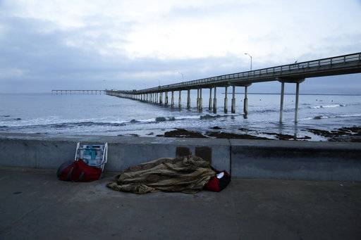 "In this Sept. 28, 2017 photo, a person sleeps under a blanket on a beach near the Ocean Beach Pier in San Diego. In a place that bills itself as ""America's Finest City,� renowned for its sunny weather, surfing and fish tacos, spiraling real estate values have contributed to spiraling homelessness."