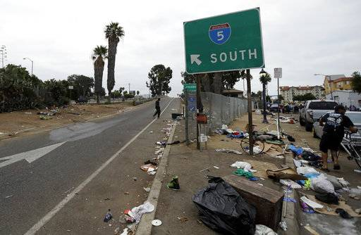 "In this Sept. 19, 2017 photo, trash from homeless encampments lines an entrance ramp for Interstate Highway 5 in San Diego. In a place that bills itself as ""America's Finest City,� renowned for its sunny weather, surfing and fish tacos, spiraling real estate values have contributed to spiraling homelessness in San Diego. Most alarmingly, the explosive growth in the number of people living outdoors has contributed to a hepatitis A epidemic."