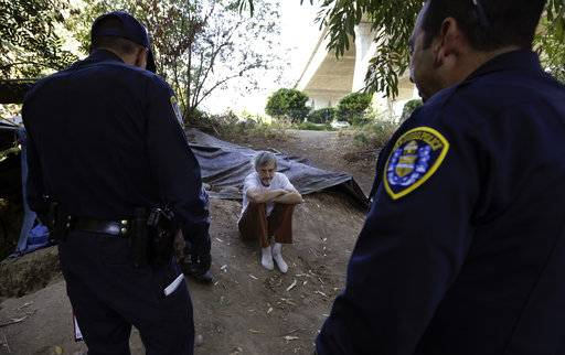 "In this Sept. 28, 2017, photo, Stephen Schofield looks on as police officials encourage him to get a Hepatitis A vaccination near where is living along the San Diego River in San Diego. A recent Hepatitis A outbreak - the worst epidemic of its kind in 20 years in the United States - reflects how much homelessness has become a crisis in San Diego, a top tourist destination known for its sunny weather, surfing and fish tacos that bills itself as ""America's Finest City."""