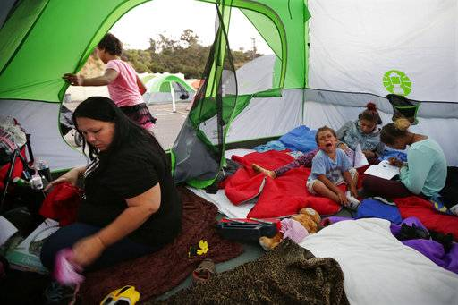 In this Oct. 18, 2017, photo, Christine Wade, left, sorts clothing as Roland, 4, cries and sisters Shawnni, 12, right, and Shaccoya, 14, draw in the family's tent provided by the city in a sanctioned encampment in San Diego. The Wade family is among several hundred people living in the city's first campground open for the homeless, set up to curb the worst Hepatitis A outbreak in the United States in decades. The new camp, in a parking lot on the edge of sprawling Balboa Park, reflects the severity of the homeless crisis gripping cities along the west coast.