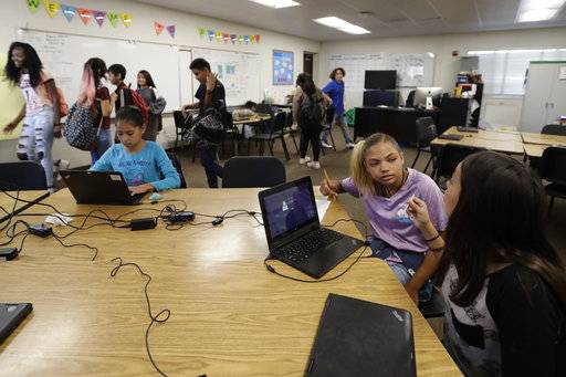 In this Oct. 24, 2017, photo, Shawnni Wade, 12, second from right, talks with a friend at Perkins Elementary School in San Diego. Perkins has a playground with a panoramic view of sleek high-rises and the shiny dome of the city's new central library; it also has a student body that is more than a quarter homeless, up from 4 percent three years ago.