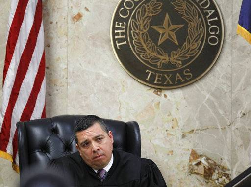92nd state District Court Judge Luis Singleterry listens to closing arguments during John Feit's murder trial, Thursday, Dec. 7, 2017, at the Hidalgo County Courthouse in Edinburg, Texas. Feit, a former priest, is accused of suffocating Irene Garza in April 1960, after she went to confession at Sacred Heart Catholic Church in McAllen. (Nathan Lambrecht/The Monitor via AP)