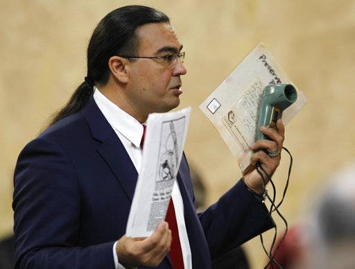 Defense attorney O. Rene Flores holds a slide viewer and statements as he presents his closing argument John Feit's murder trial, Thursday, Dec. 7, 2017, at the Hidalgo County Courthouse in Edinburg, Texas. Feit, a former priest, is accused of suffocating Irene Garza in April 1960, after she went to confession at Sacred Heart Catholic Church in McAllen. (Nathan Lambrecht/The Monitor via AP)