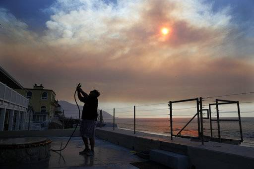 Steve Andruszkiewicz waters down his beach house as the sun is visible through thick smoke from a wildfire at Faria State Beach in Ventura, Calif., Thursday, Dec. 7, 2017. The wind-swept blazes have forced tens of thousands of evacuations and destroyed dozens of homes.