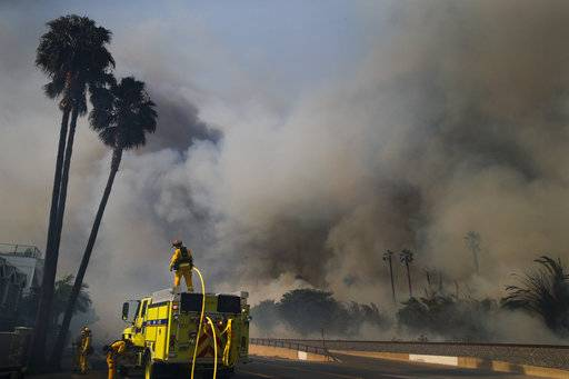 Firefighters battle a wildfire as smoke rises from burning palm trees at Faria State Beach in Ventura, Calif., Thursday, Dec. 7, 2017. The wind-swept blazes have forced tens of thousands of evacuations and destroyed dozens of homes.